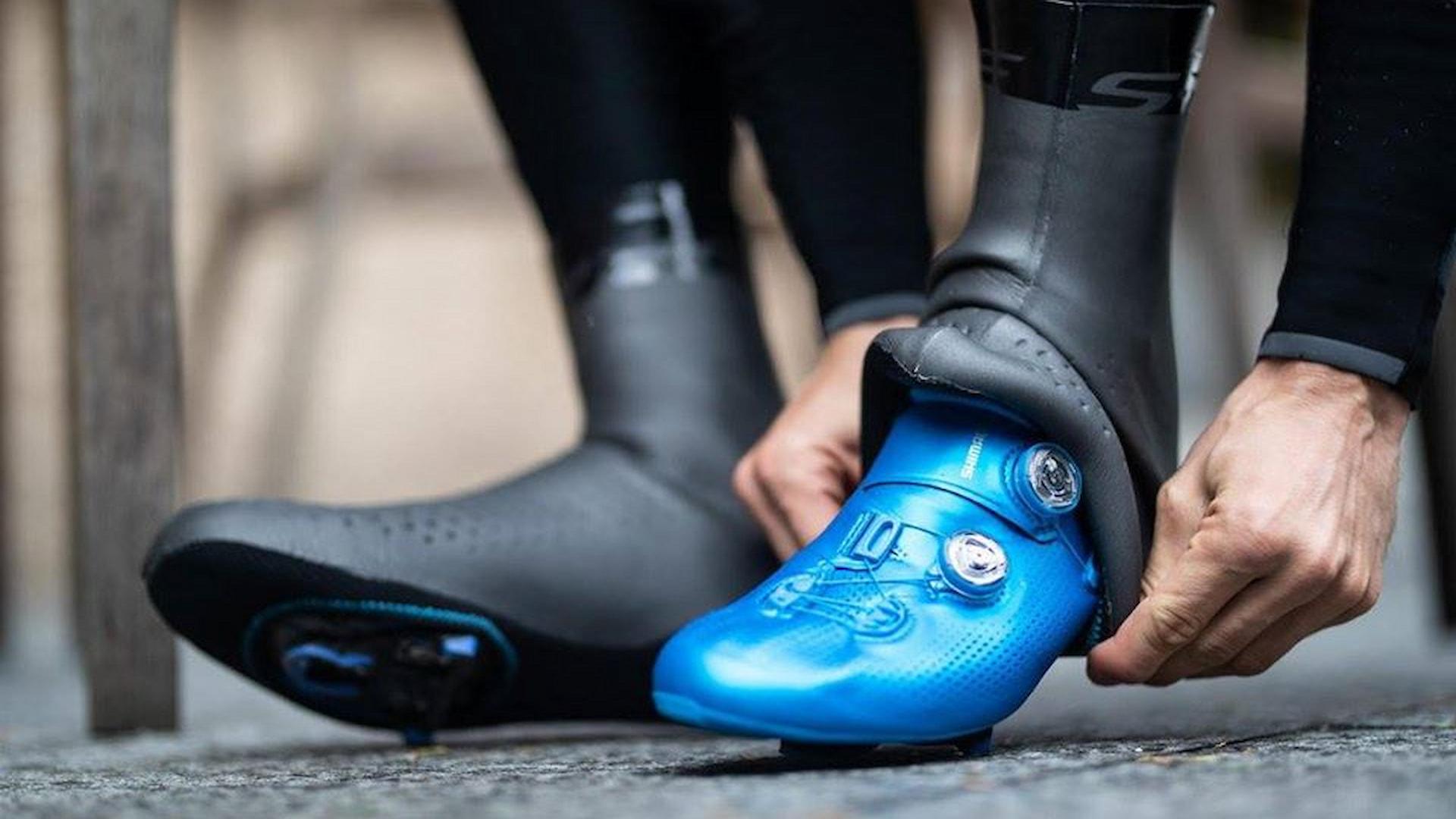 Buty rowerowe wraz z ochraniaczami zakładane przez kolarza